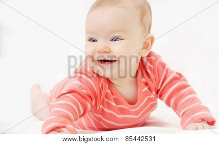 Adorable Cute Little Girl With Big Blue Eyes And Wide Smile Playing On The Sofa