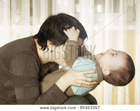 Caucasian Mother And Her Baby Playing Together At Home