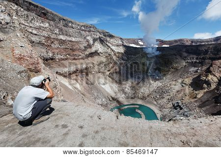 Tourist In Crater Active Gorely Volcano Shoot Of Volcano Acting Fumarole And Crater Lake. Kamchatka
