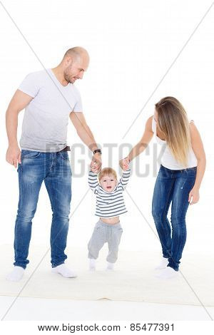 Happy young parents helping their little son doing the first steps. poster