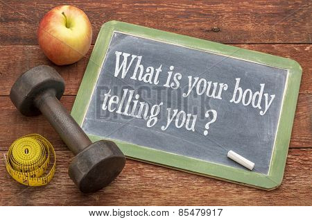 What is your body telling you?  A question on a slate blackboard against weathered red painted barn wood with a dumbbell, apple and tape measure