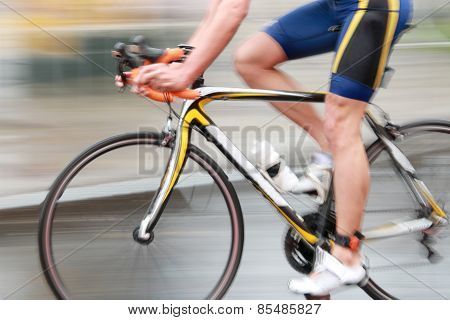 Side view of a very rapid professional male cyclist without torso dressed in a blue sport suit. Motion blur poster