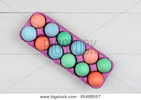 A pink one dozen carton of dyed Easter Eggs on a white wood kitchen table. Horizontal format with the carton at an angle. Overhead view.