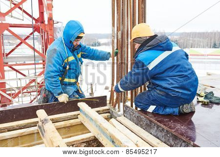 construction workers installing framework for concrete at building area