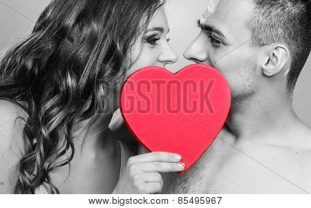 Romantic Couple Kissing Behind Red Heart