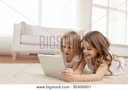 children, technology and home concept - two little girls with tablet pc computer lying on floor at home
