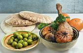 Moroccan duck leg tagine with tangerines onions and fresh cilantro served with pita bread and green olives. poster