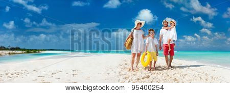 Panorama of happy beautiful family with kids walking together on tropical beach during summer vacation