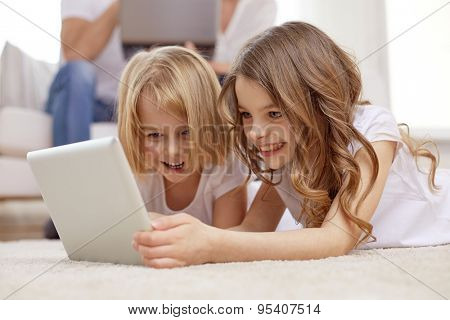 people, family, technology and children concept - happy little girls playing with tablet pc computer at home