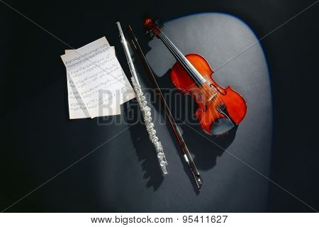 Violin and flute with music notes on dark background poster