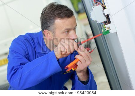 Electrician prodding around at a fusebox