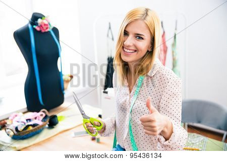 Smiling female tailor standing in workshop and showing thumb up