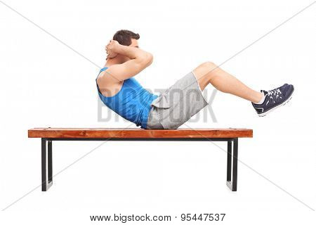 Young male athlete doing stomach crunches on a wooden bench isolated on white background
