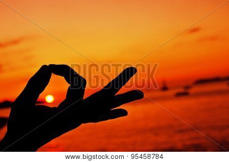 closeup of a young man meditating with his hands in gyan mudra at sunset