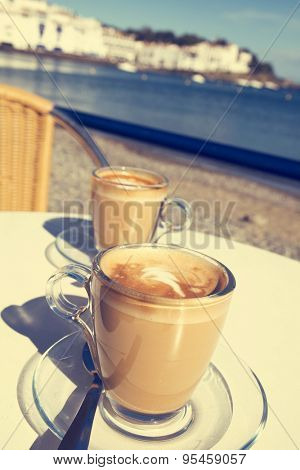 closeup of two glasses with caffe macchiato on a table in the terrace of a cafe in the seafront of Cadaques, in the Costa Brava, Spain