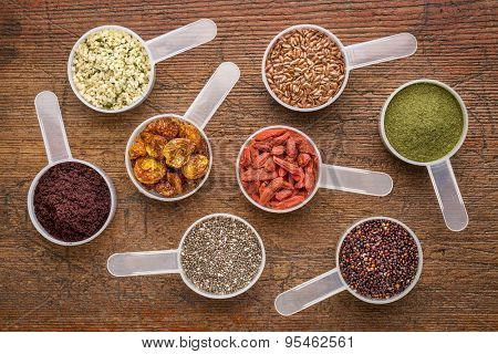 superfood abstract (wheatgrass, acai berry, goji berry, falx seed,chia seed,goldenberry,hemp seed, quinoa grain) - top view of measuring scoop against rusti wood