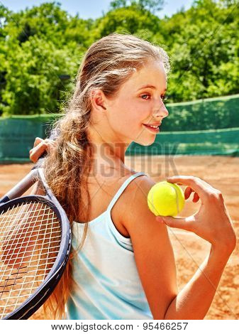 Girl teen sportsman in blue shirt swith racket and ball  on  tennis court.