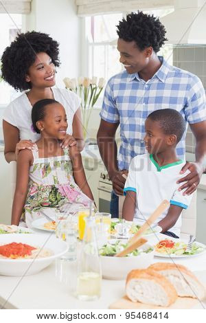 Happy family sitting down to dinner together at home in the kitchen