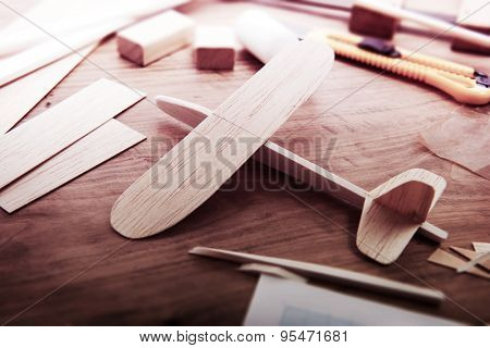 Making model airplane from wood. Wooden air plane handcrafted with balsa wood, on work table. tools and Materials on table. Intentionally shot in retro-impression color, and shallow depth of field.