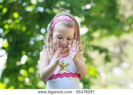 Happy curly toddler girl is clapping with her palms poster