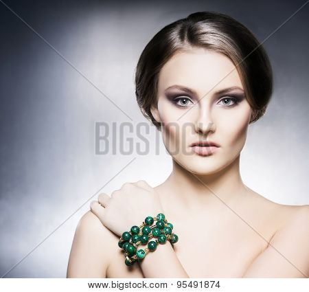 Young, beautiful and rich woman in jewels. Metal background  poster