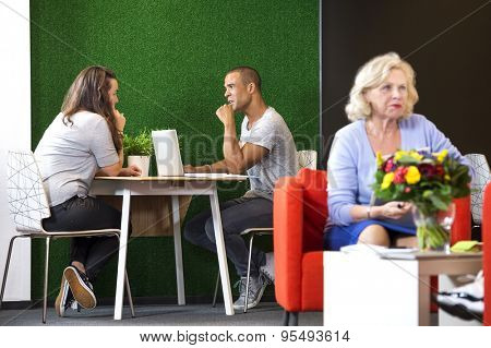 Businesspeople discussing while sitting at table in modern office lobby poster
