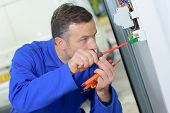 Electrician prodding around at a fusebox poster