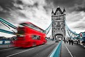 Red bus in motion on Tower Bridge in London, the UK. Dramatic rainy clouds. Black and white with red and blue bridge elements. poster