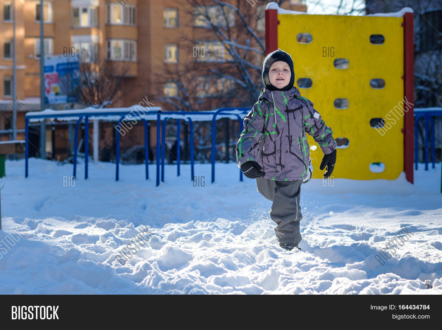 Portrait of happy cute little kid boy in colorful warm winter fashion  clothes. Funny child having fun in winter forest or park on cold day.  trowing ice and ... 900c332c9