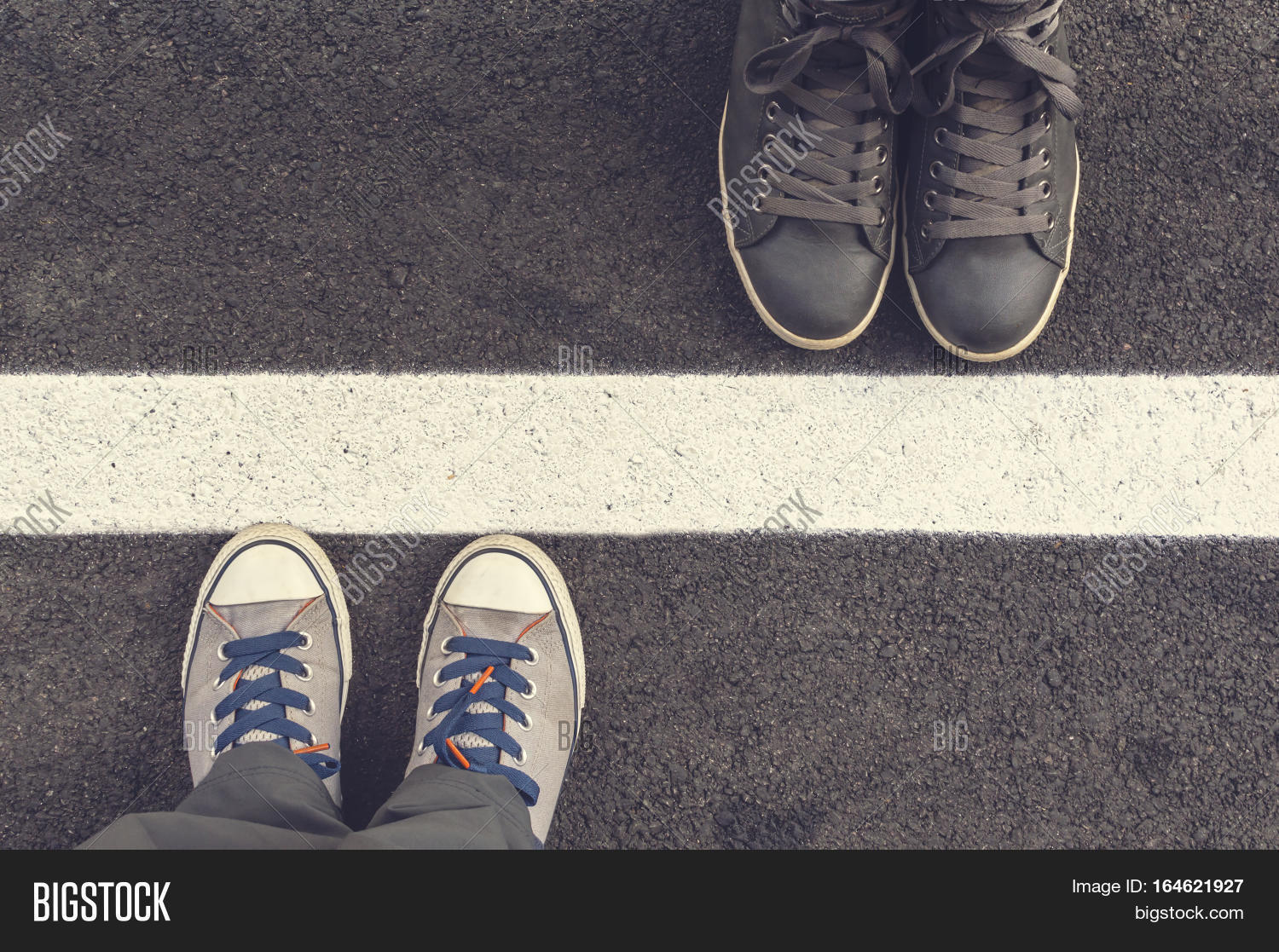 Two Pair Of Sneakers On A Asphapt Road Top View