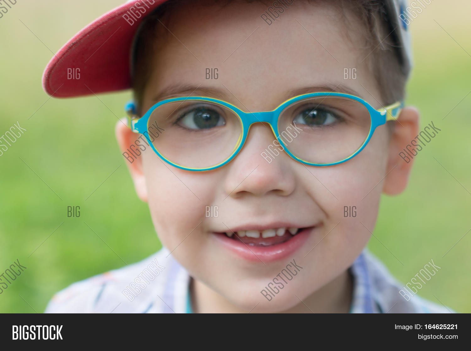 f631d596655d Happy little cute boy in glasses and cap at summer day outdoor closeup