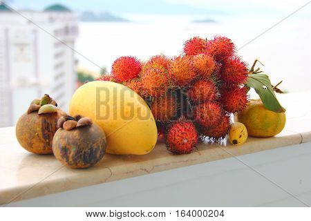 on the railing of the balcony arrangement of exotic fruit, rambutan, mangosteen, mango, tangerine, visible behind the background of the sea, mountains, hotels