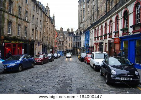 Edinburgh, United Kingdom - June 16, 2014. The cobbled curve of shop-lined Victoria St in Edinburgh, with historical buildings, commercial properties, cars and people.