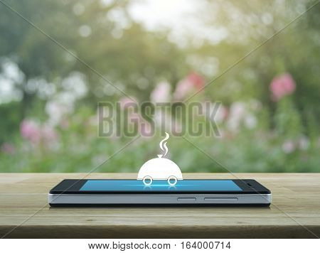 Restaurant cloche flat icon on modern smart phone screen on wooden table over blur pink flower and tree Food delivery concept
