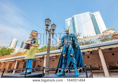Hong Kong, China - December 5, 2016: Old Master Q and Lord Dragon, statues of famous characters, in Hong Kong Avenue of Comic Stars, Kowloon Park. Urban skyline background of Tsim Sha Tsui District.