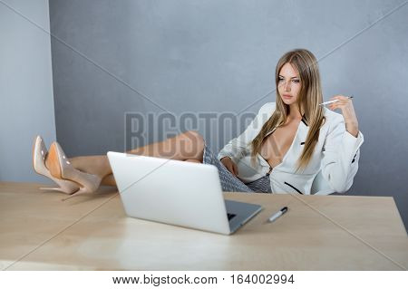 Attractive sexy business woman or secretary with notebook computer pc wearing white suit with decollete big breast sitting on chair, legs on table against copy space gray wall background web camera chating surfing internet looking in monitor