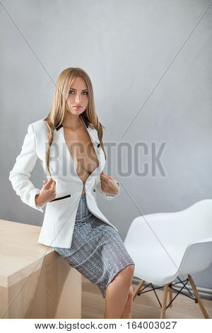 Portrait of gorgeous young caucasian attractive sexy business woman or secretary wearing white suit with decollete big breast sitting on table against copy space gray wall background with chair looking at camera.