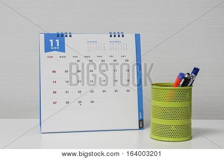 November calendar with pen and stationary box to arrange meeting