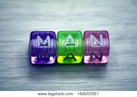 many-colored word MAN of plastic cubics and white chars