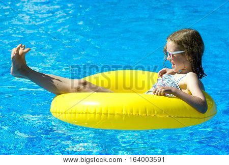 Little Girl With Inflatable Rubber Ring Having Fun In Swimming Pool.