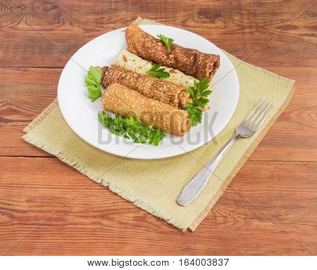 Pancakes filled with meat filling and parsley twigs on a white dish and fork on a cloth napkin on an old wooden surface