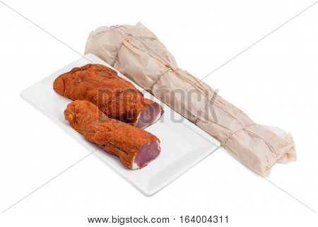 Two pieces of dried pork tenderloin on a rectangular dish and beside it dried pork tenderloin wrapped in parchment paper on a light background