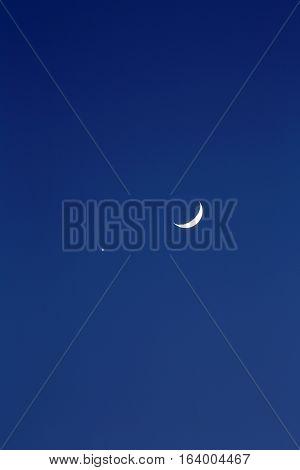 Crescent moon and planet venus, dark blue background