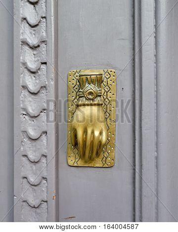 door detail hand shaped bronze knocker closeup