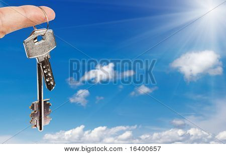 Finger with key against blue sky background