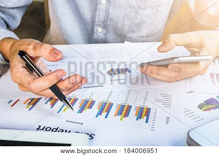Businessman discussing the analysis charts or graphs on modern White office desk table and using smart phone.Business concept.