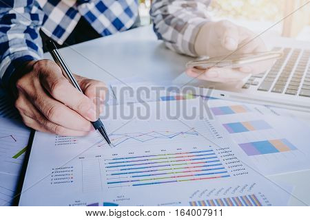 Businessman working with smart phone and discussing the analysis charts or graphs on modern White office desk table .Close up business team analysis and strategy concept with sun flare.