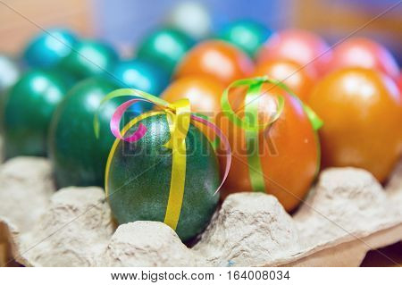 Brightly colored decorated Easter eggs in egg carton holder, holiday background