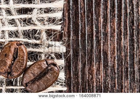 Roasted coffee beans on sackcloth dark rough wood surface. Super macro view