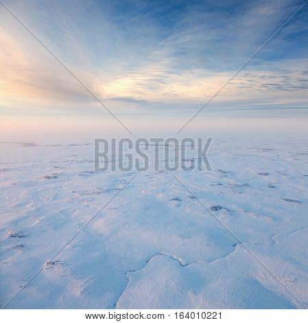 Aerial view above the snow-covered space of endless tundra in time of short cold winter day.